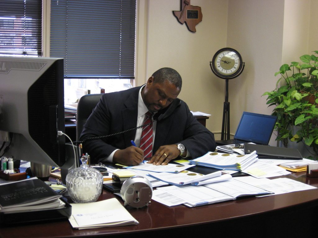 The Dallas County Clerk doing paperwork at his desk